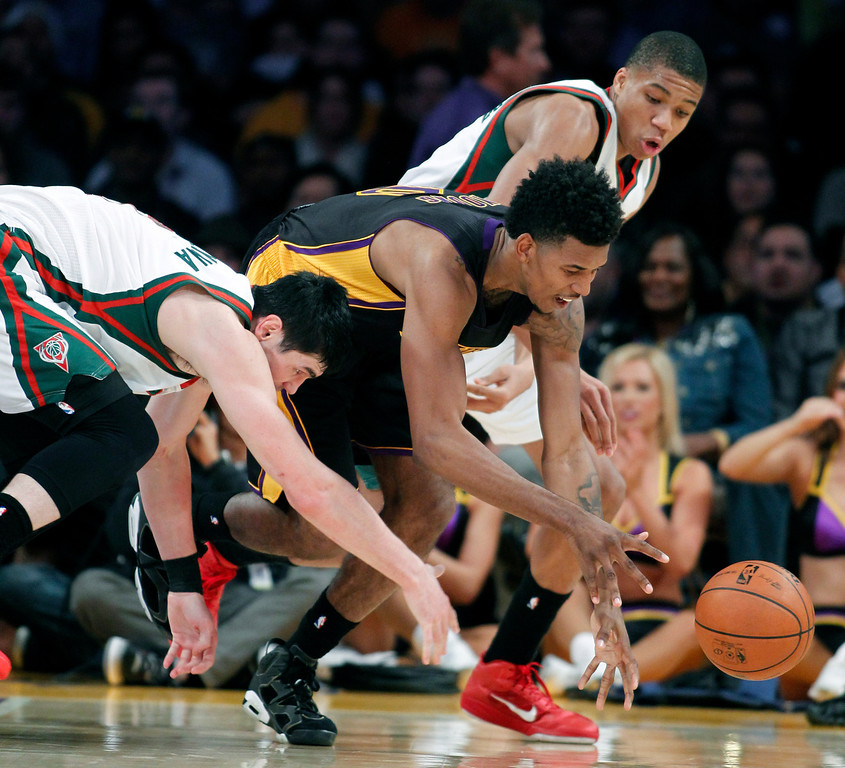 . Los Angeles Lakers forward Nick Young, center, goes for the steal as Milwaukee Bucks forward Ersan Ilyasova, left, of Turkey and shooting guard Giannis Antetokounmpo, above right, of Greece, battle for the ball during the first half of an NBA basketball game Tuesday, Dec. 31, 2013, in Los Angeles. (AP Photo/Alex Gallardo)