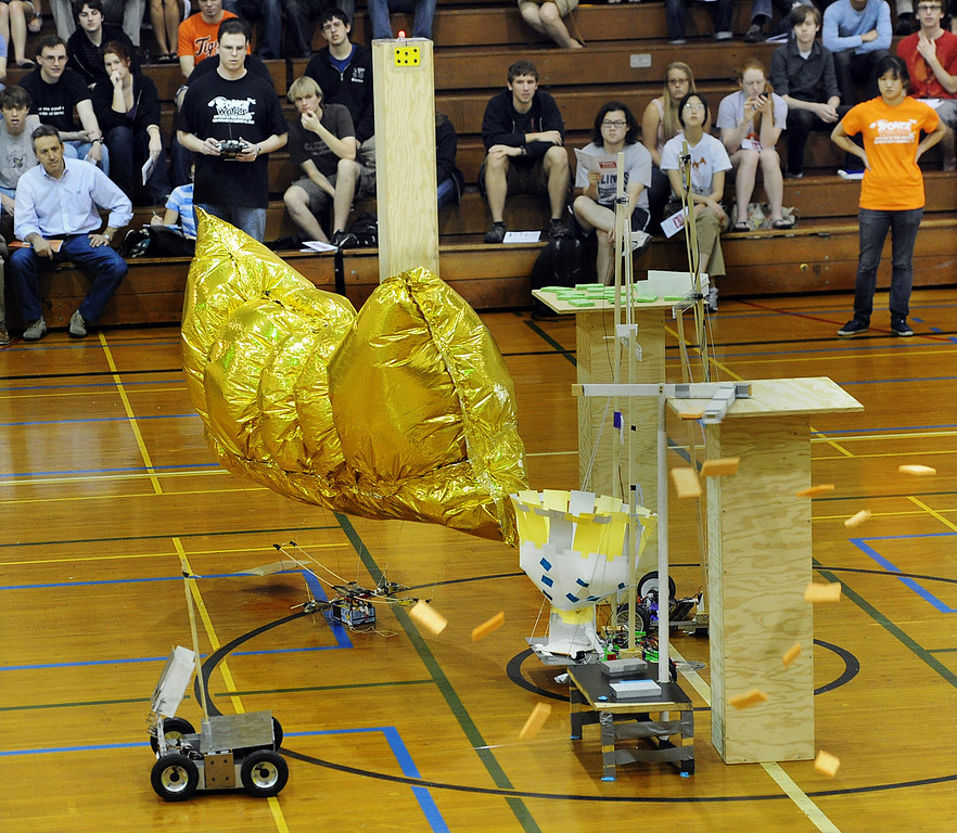 """. Team: Spongebot MetalPants sweeps sponges off a podium into their robot basket for big time score during competition at 28th Annual ME72 Engineering Design Contest, \""""Sponge Wars Attack of the Drones\"""" at Caltech Brown Gym Tuesday, March 13, 2013. Mechanical Engineering 72 competition features teams maneuvering kitchen sponges into a goal with a pair of autonomous robotic vehicles � and preventing opposing teams from doing the same. Six teams  competed head-to-head in a series of rounds. The team with the most points at the end of each heat wins. The victors earn the admiration of the crowds in the stands and are honored with the ME-72 trophy. (Photo by Walt Mancini/SXCity)"""