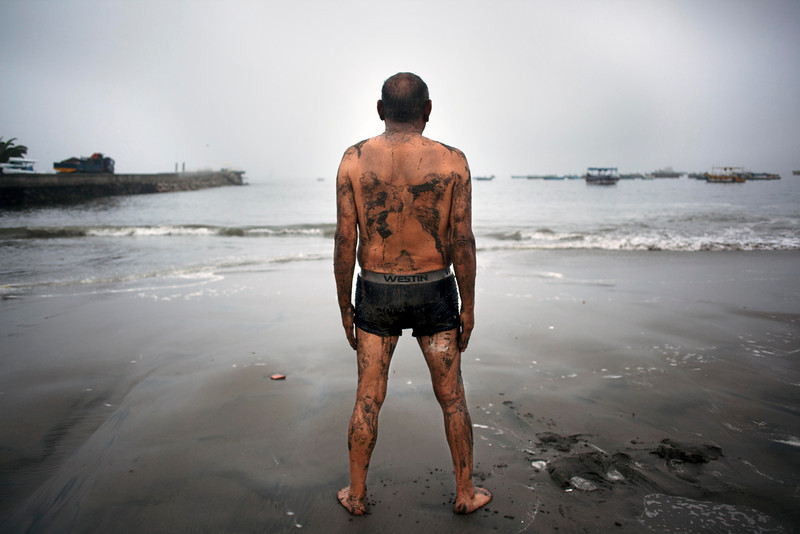 . Teodocio Perez, 71, covered with a thin layer of wet sand, looks out at the Pacific Ocean during his morning exercises on the Playa de Pescadores shore in Lima, Peru, Wednesday, April 2, 2014. Authorities lifted tsunami warnings for Chile�s long coastline early Wednesday. Six people were crushed to death or suffered fatal heart attacks, a remarkably low toll for such a powerful shift in the Earth�s crust. (AP Photo/Rodrigo Abd)