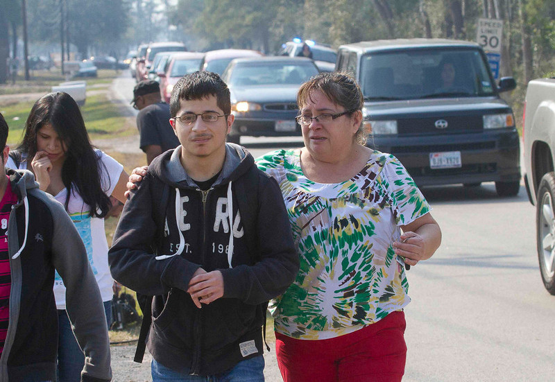 . A mother joins her son as he evacuates on foot from the Lone Star College North Harris campus in Houston, Texas, January 22, 2013. A shooting broke out between two people on the campus on Tuesday and there were three injuries, including one of the shooters, police and a school spokesman said. REUTERS/Richard Carson
