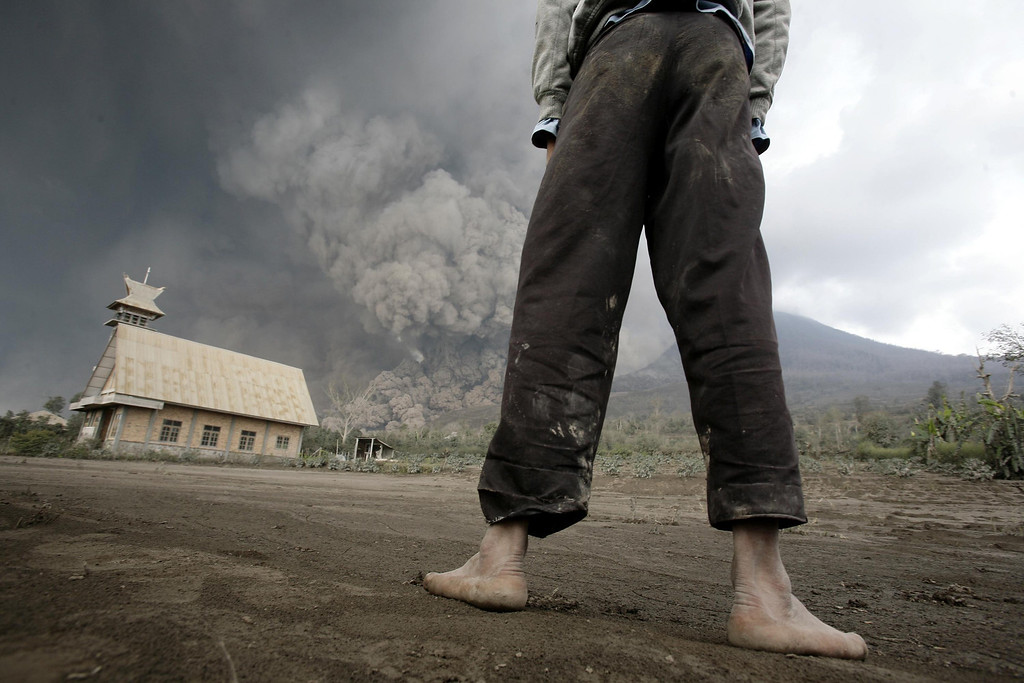 . A resident looks on at giant volcanic ash clouds from a village in Karo district during the eruption of Mount Sinabung volcano located in Indonesia\'s Sumatra island on February 1, 2014. Fourteen people, including four schoolchildren, were killed February 1 after they were engulfed by scorching ash clouds spat out by Indonesia\'s Mount Sinabung in its biggest eruption in recent days, officials said.  AFP PHOTO / CHAIDEER MAHYUDDIN/AFP/Getty Images
