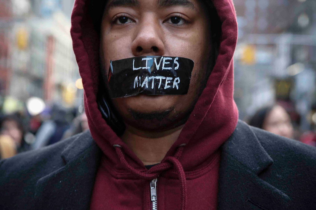 . A man with tape on his mouth marches in the National March Against Police Violence, which was organized by National Action Network, down 14th St on December 13, 2014 in New York City. The march coincided with a march in Washington D.C. and comes on the heels of two grand jury decisions not to indict white police officers in the deaths of two unarmed black men. (Photo by Kena Betancur/Getty Images)