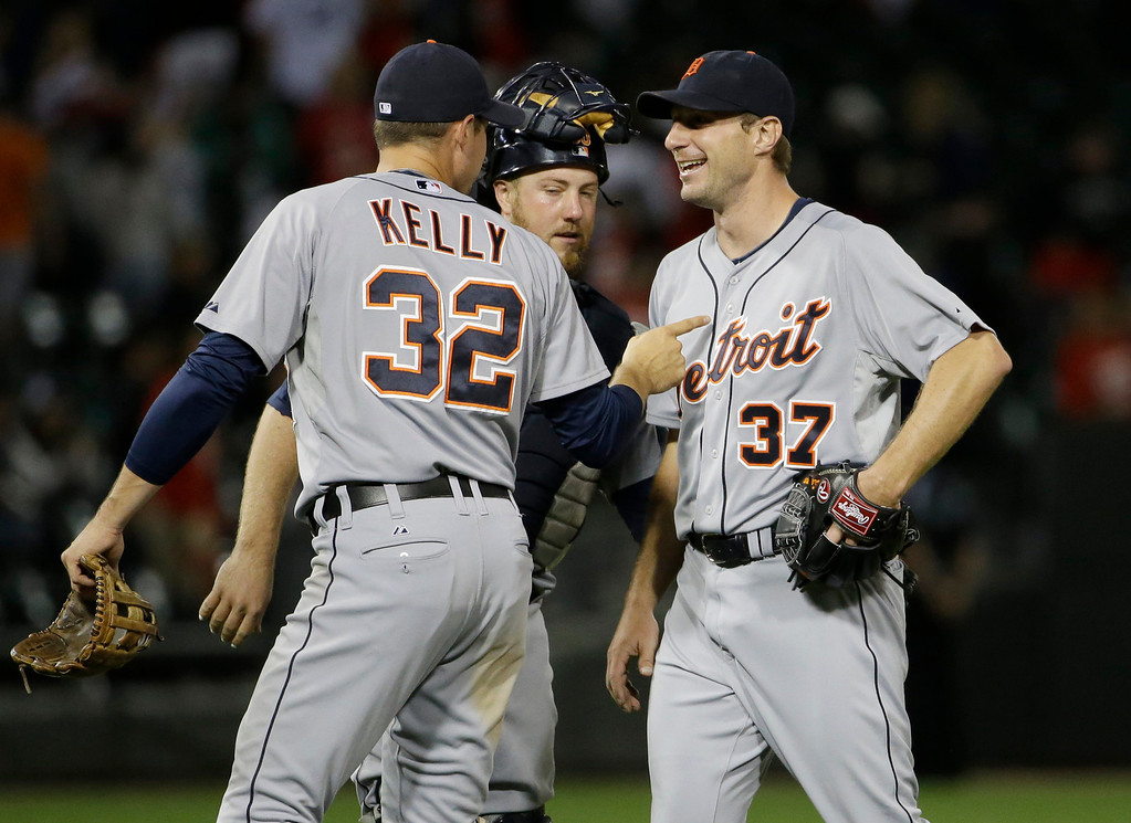 . Detroit Tigers starter Max Scherzer, right, celebrates with catcher Bryan Holaday and Don Kelly (50) after the Tigers defeated the Chicago White Sox 4-0 in a baseball game in Chicago on Thursday, June 12, 2014. (AP Photo/Nam Y. Huh)
