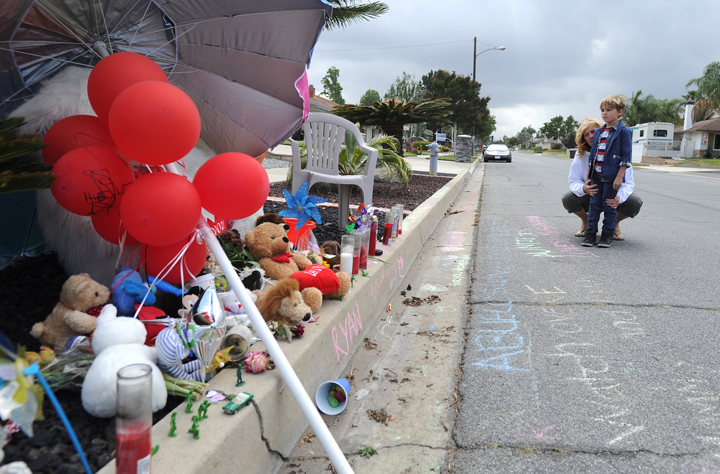 . Cathy Hamilton and her grandson Judah of Rancho Cucamonga, visit the memorial site for Ryan Cruz Saldana, 3, who was hit by a truck and killed Friday, on Alta Loma Drive, May 7, 2014. (Photo by John Valenzuela/Inland Valley Daily Bulletin)