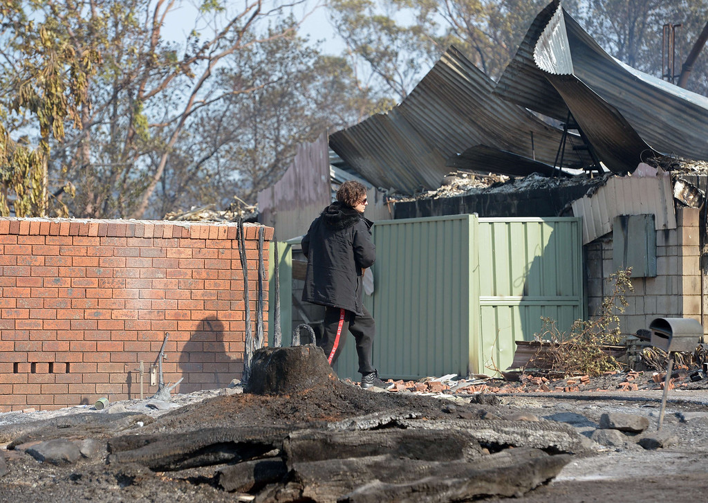 . A man (C) walks near houses destroyed by bush fires at Winmalee in Sydney\'s Blue Mountains on October 18, 2013.  AFP PHOTO / Greg WOOD/AFP/Getty Images