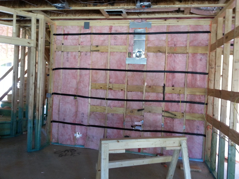 You can see where the fridge will go on the left and the three horizontal rows of boards where the cabinets will be attached.  Stove/Oven in the middle below the vent.