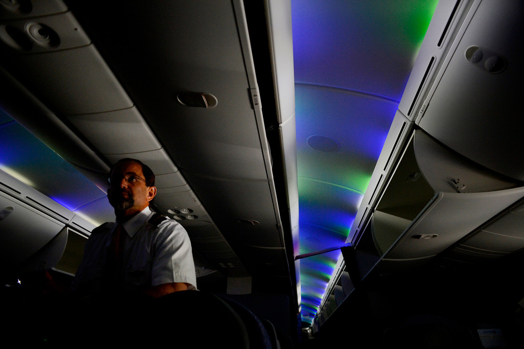 . Flight attendant Brian McCarthy talks about the Boeing 787 Dreamliner while preparing for departure to Houston at Denver International Airport in Denver, CO May 21, 2013. The LED lights can simulate sunrise and sunset. It is the first flight from Denver after a delay caused by battery failures. The first international flight between DIA and Tokyo is scheduled for June 10. (Photo By Craig F. Walker/The Denver Post)