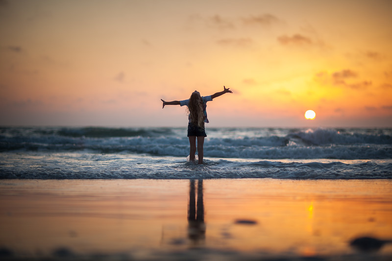 Woman standing on the ocean shore.