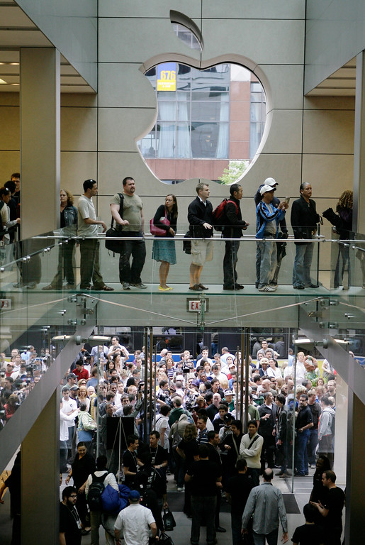 . Customers rush into the Apple Store in downtown Chicago Friday, June 29, 2007, to purchase the company\'s new iPhone, a gadget that combines the functions of a cell phone, iPod media player and wireless Web browser.  Apple is banking on the new do-everything phone with a touch-sensitive screen to become its third core business next to its moneymaking iPod players and Macintosh computers. (AP Photo/M. Spencer Green)