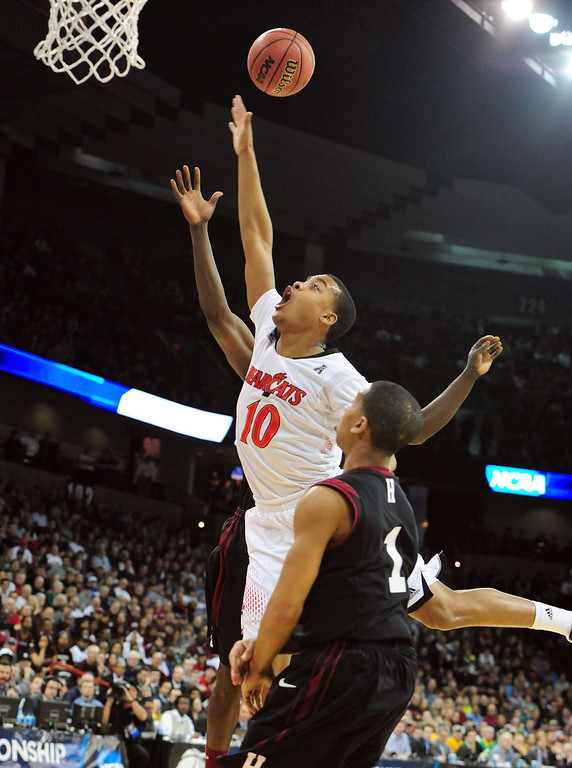 . Troy Caupain #10 of the Cincinnati Bearcats goes up against the Harvard Crimson during the second round of the 2014 NCAA Men\'s Basketball Tournament at Spokane Veterans Memorial Arena on March 20, 2014 in Spokane, Washington.  (Photo by Steve Dykes/Getty Images)
