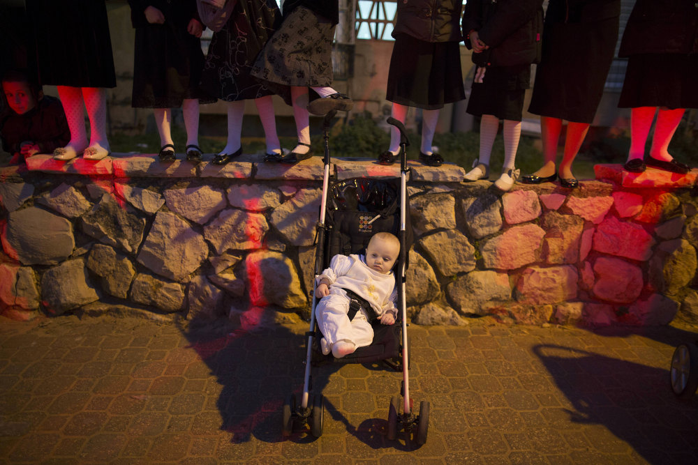 . A child rests as Ultra-Orthodox Jewish children stand on the edge of a stone wall to watch the wedding celebrations of the great-grandson of the Rabbi of the Tzanz Ultra-Orthodox Hasidic community in Netanya, on January 2, 2013. MENAHEM KAHANA/AFP/Getty Images