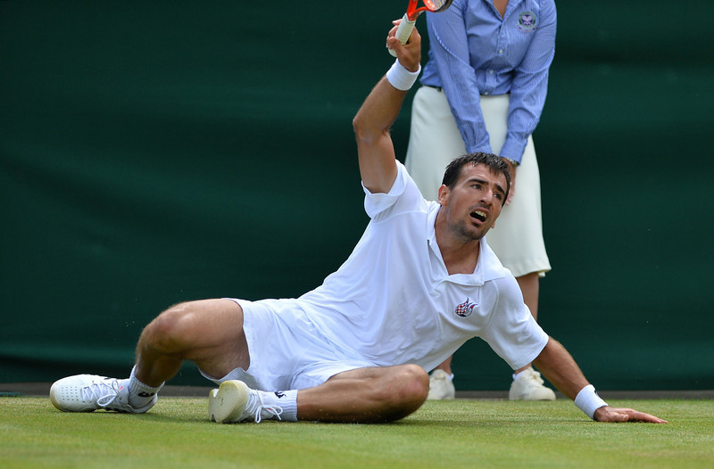 . Croatia\'s Ivan Dodig slips after hitting a return against Spain\'s David Ferrer during their fourth round men\'s singles match on day seven of the 2013 Wimbledon Championships tennis tournament at the All England Club in Wimbledon, southwest London, on July 1, 2013. BEN STANSALL/AFP/Getty Images