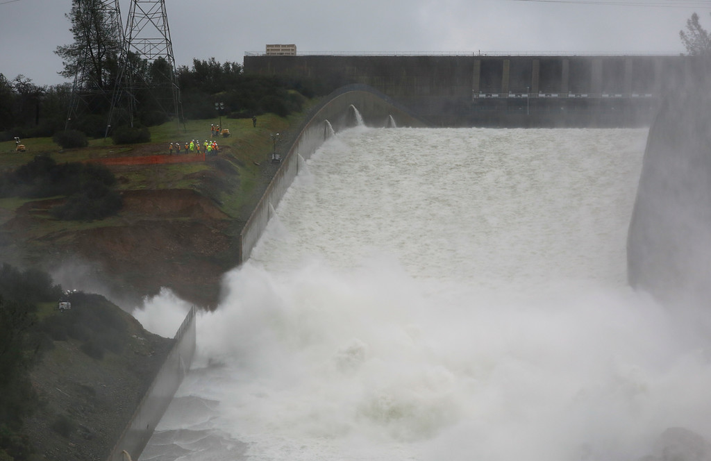 . Water flows through break in the wall of the Oroville Dam spillway, Thursday, Feb. 9, 2017, in Oroville, Calif. Earlier this week, chunks of concrete went flying off the spillway, creating a 200-foot-long, 30-foot deep hole that continues to grow. (AP Photo/Rich Pedroncelli)