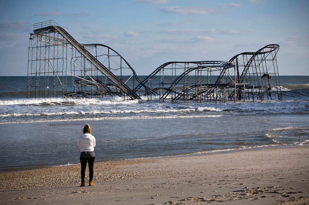 . A woman looks at a roller coaster sitting in the ocean, when the boardwalk it was built upon collapsed during Hurricane Sandy, in Seaside Heights, New Jersey November 28, 2012. The storm made landfall along the New Jersey coastline on October 29, 2012 - one month ago tomorrow. REUTERS/Andrew Burton