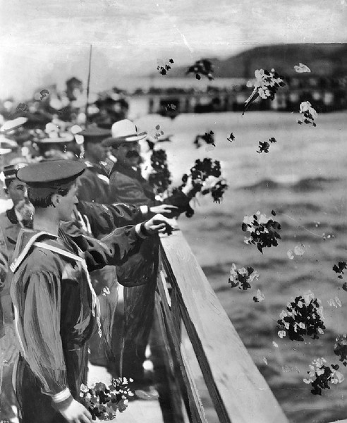 Navy men and civilians casting flowers into the sea at the Santa Monica pier, 1925-1935