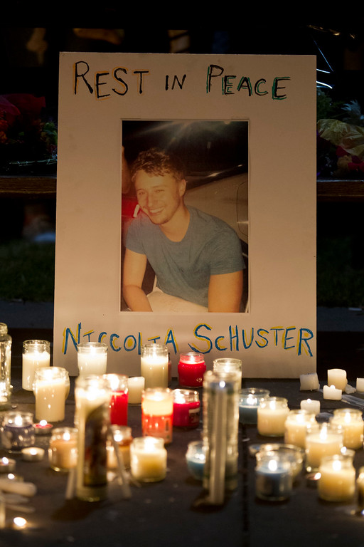 . Candles illuminate a picture of Niccolai Schuster during a candlelight vigil for six Irish students Wednesday, June 17, 2015, in Berkeley, Calif. The six Irish students died when a balcony collapsed during a party.  (AP Photo/Beck Diefenbach)