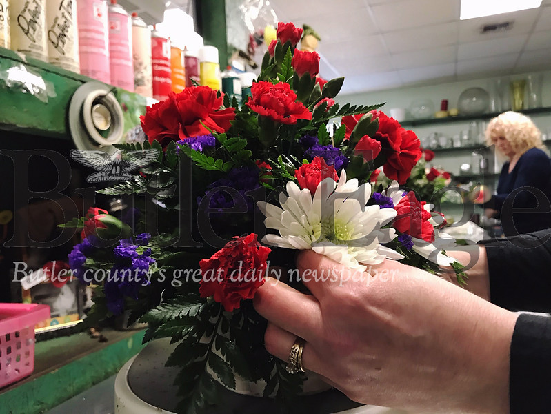 Michele Craig, a floral designer at Bortmas, the Butler Florist, arranges daises and carnations into a traditional floral arrangement set in a wicker basket.