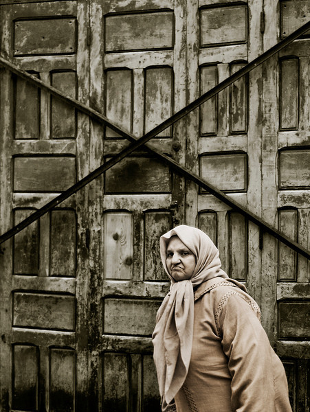 A not to happy woman walking past an old door inside the Medina.
