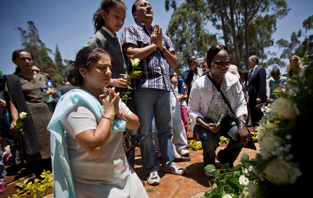 . Relatives of those who died lay white roses and pray at a stone memorial, during a memorial service marking the one-month anniversary of the Sept. 21 Westgate Mall terrorist attack, in Karura Forest in Nairobi, Kenya Monday, Oct. 21, 2013.  (AP Photo/Ben Curtis)