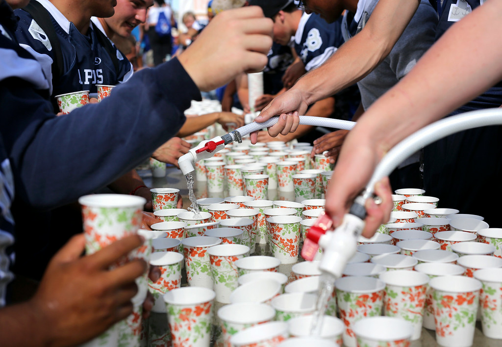 . Aptos Mariners football players fill hundreds of paper cups with water at Capitola Beach on Sunday after the Wharf to Wharf race. (Kevin Johnson -- Santa Cruz Sentinel)