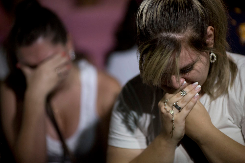 Description of . Women react during a march near the Kiss nightclub honoring the victims of early Sunday's fatal fire inside the club in Santa Maria, Brazil, Monday, Jan. 28, 2013. All the elements were in place for the tragedy at the Kiss nightclub early Sunday. The result was the world's worst fire of its kind in more than a decade, with 231 people dead and this southern Brazilian college town in shock and mourning. (AP Photo/Felipe Dana)
