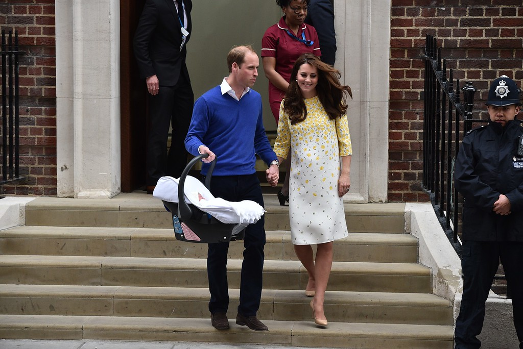 . Britain\'s Prince William, Duke of Cambridge, carries his newly-born daughter, his second child, in a car seat as he walks with his wife Catherine, Duchess of Cambridge, away from the Lindo Wing at St Mary\'s Hospital in central London, on May 2, 2015.  The Duchess of Cambridge was safely delivered of a daughter weighing 8lbs 3oz, Kensington Palace announced. The newly-born Princess of Cambridge is fourth in line to the British throne. AFP PHOTO / LEON NEAL