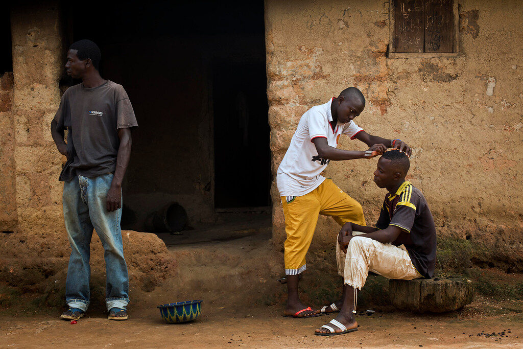 . In this photo taken Saturday Nov. 22, 2014, a man gets his hair cut in the Guinean village of Meliandou, some 400 miles (600 kms) south-east of Conakry, Guinea. Meliandou, a small village at the top of a forested hill reached by a rutted red earth track, is notorious as the birthplace and crucible of the most deadly incarnation of the Ebola virus to date. (AP Photo/Jerome Delay)