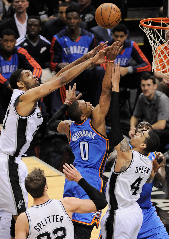 . Oklahoma City Thunder guard Russell Westbrook (0) chases a rebound against San Antonio Spurs\' Tim Duncan, left, Danny Green, right, and Tiago Splitter, of Brazil, during the first half of Game 2 of a Western Conference finals NBA basketball playoff series, Wednesday, May 21, 2014, in San Antonio. (AP Photo/Darren Abate)