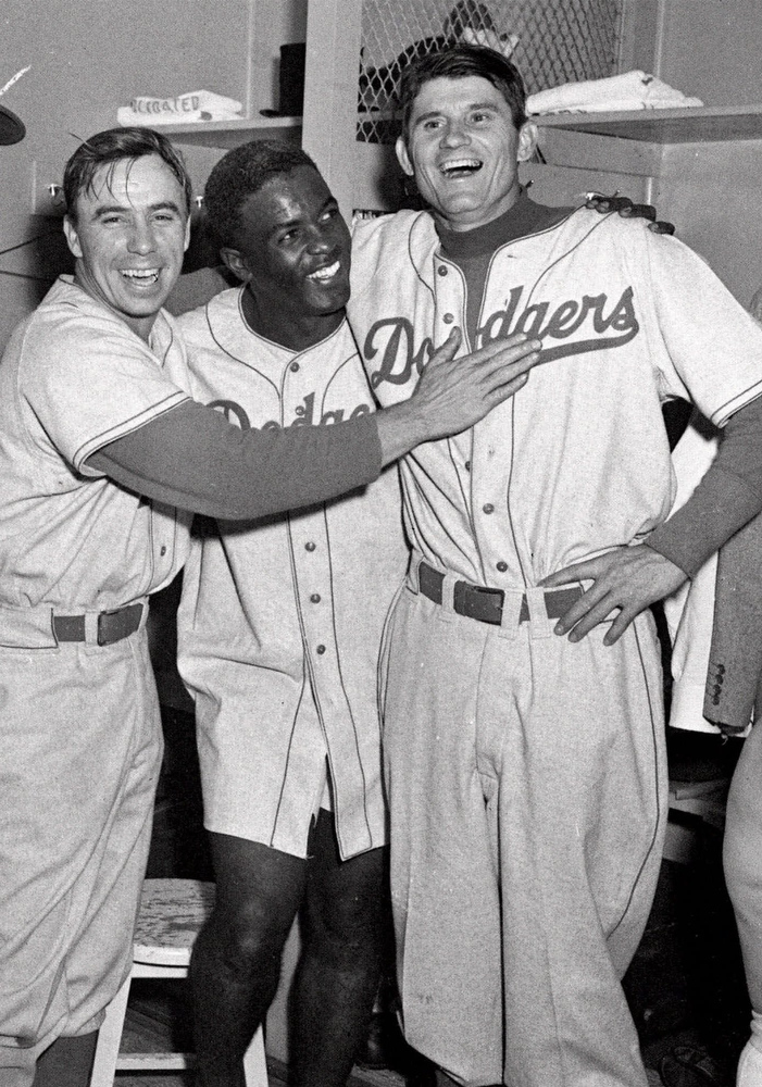 Description of . Brooklyn Dodgers from left, Pee Wee Reese, Jackie Robinson, and Preacher Roe are a happy trio in the clubhouse after the Dodgers beat the Yankees 5-3 in the third game of the World Series at Yankee Stadium in New York City, in this Oct. 3, 1952 photo. (AP Photo)