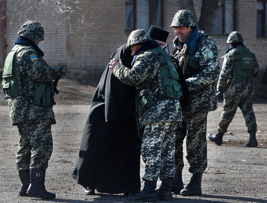 . A priest blesses Ukrainian border guards at a military camp in the village of Alekseyevka on the Ukrainian-Russian border, eastern Ukraine, Friday, March 21, 2014. Russian President Vladimir Putin has signed a resolution approved by parliament to annex Crimea. (AP Photo/Sergei Grits)