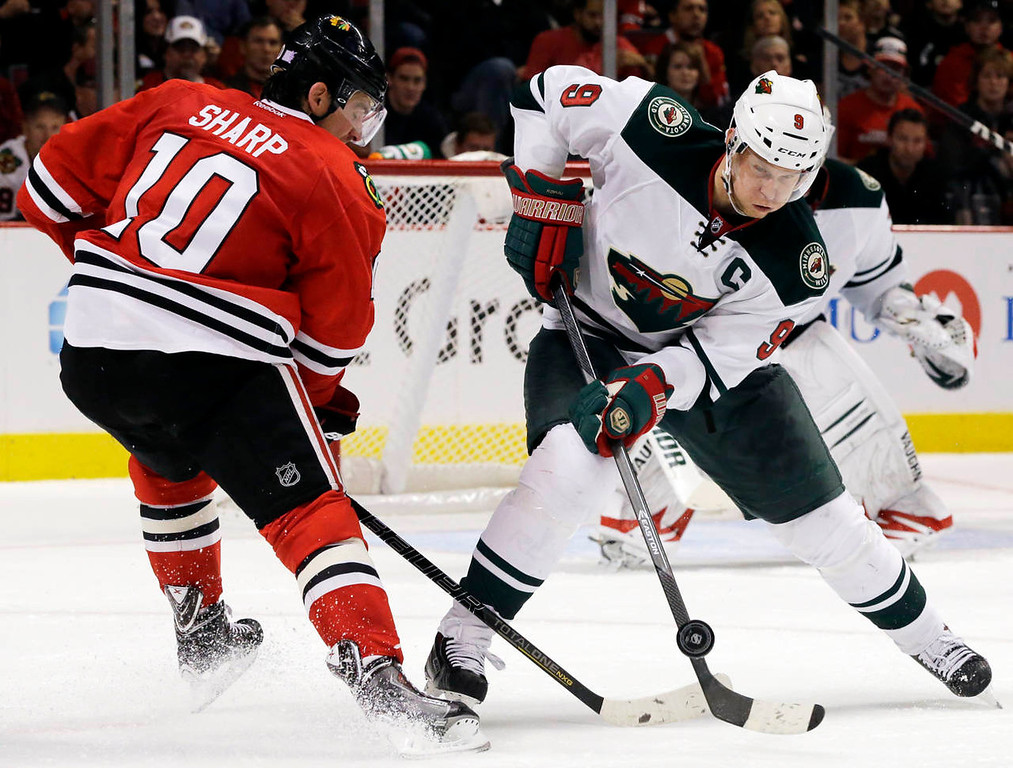 . Minnesota Wild\'s Mikko Koivu (9) controls he puck against Chicago Blackhawks\' Patrick Sharp (10) during the second period. (AP Photo/Nam Y. Huh)