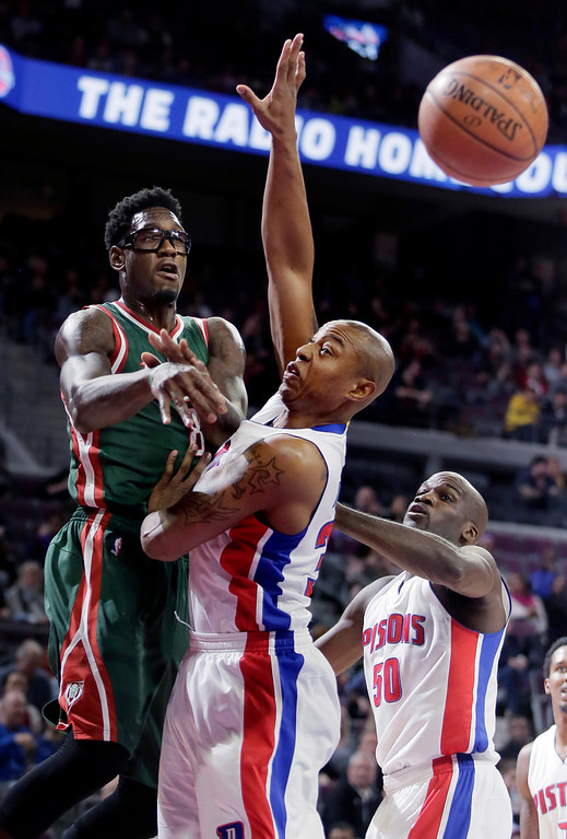 . Milwaukee Bucks\' Larry Sanders, left, passes the ball while being defended by Detroit Pistons\' Caron Butler, right, during the first half of an NBA basketball game Friday, Nov. 7, 2014, in Auburn Hills, Mich. (AP Photo/Duane Burleson)