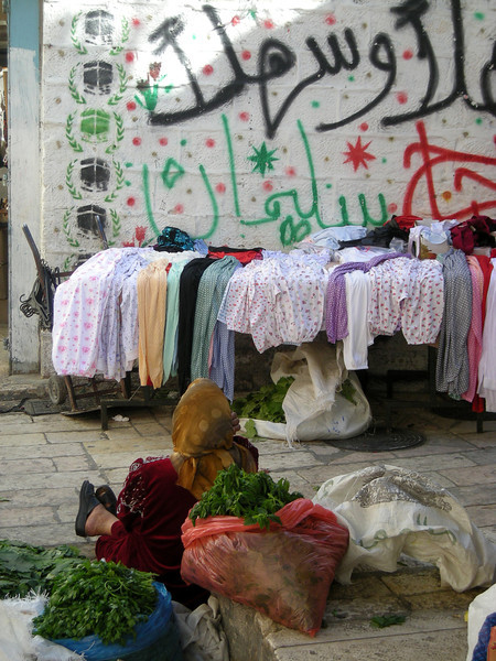 a woman selling mint and other herbs in the Muslim Quarter of the old city.   the wall opposite her announces with images of the Kabbah that someone living there had been to Mecca and completed the Haj.