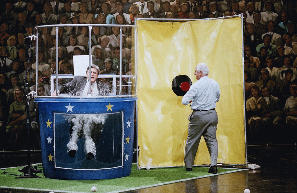 """. LENO SHOW 1993  \""""The Tonight Show\"""" host Jay Leno, left, falls in to the water tank as Los Angeles Dodgers\' manager Tommy Lasorda pushes the mark after missing it numerous times during taping of the show, June 3, 1993 in Burbank, Calif. Leno lost a bet to Lasorda that the Dodgers would win ten straight. (AP Photo/Kevork Djansezian)"""