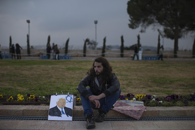 . A man sits next to a portrait of former Israeli Prime Minister Ariel Sharon as his body lies in state at Knesset Plaza on January 12, 2014 in Jerusalem, Israel.(Photo by Uriel Sinai/Getty Images)