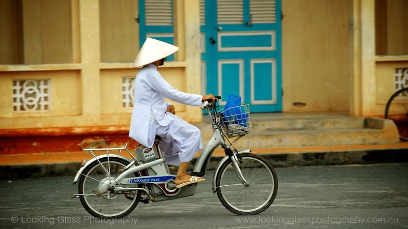 Nun riding outside Cao Dai Temple