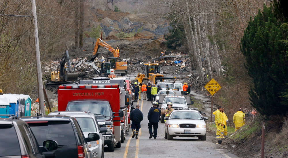 . Emergency vehicles fill Highway 530 leading to the scene of a deadly mudslide that covers the road, Wednesday, March 26, 2014, in Oso, Wash. Sixteen bodies have been recovered, but authorities believe at least 24 people were killed. And scores of others are still unaccounted for, although many of those names were believed to be duplicates or people who escaped safely. (AP Photo/Rick Wilking, Pool)