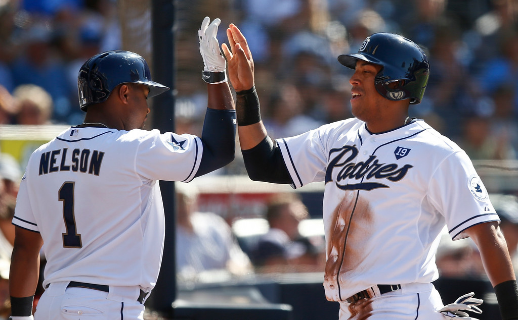 . San Diego Padres\' Yangervis Solarte high fives with Chris Nelson after scoring in the first inning of a baseball game against the Colorado Rockies Wednesday, Aug. 13, 2014, in San Diego. (AP Photo/Lenny Ignelzi)