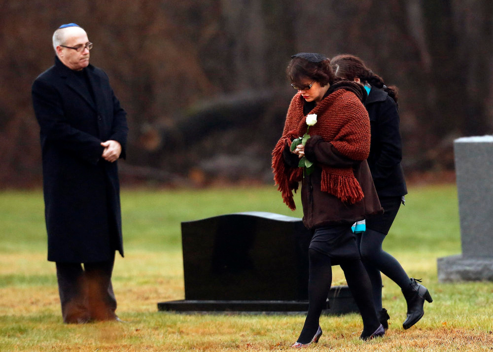 Description of . Veronique Pozner (front), mother of Sandy Hook Elementary School shooting victim Noah Pozner, arrives at his gravesite for his burial at the B'nai Israel Cemetery in Monroe, Connecticut December 17, 2012. Two funerals on Monday ushered in what will be a week of memorial services and burials for the 20 children and six adults massacred at Sandy Hook Elementary School in Newtown, Connecticut.  REUTERS/Shannon Stapleton