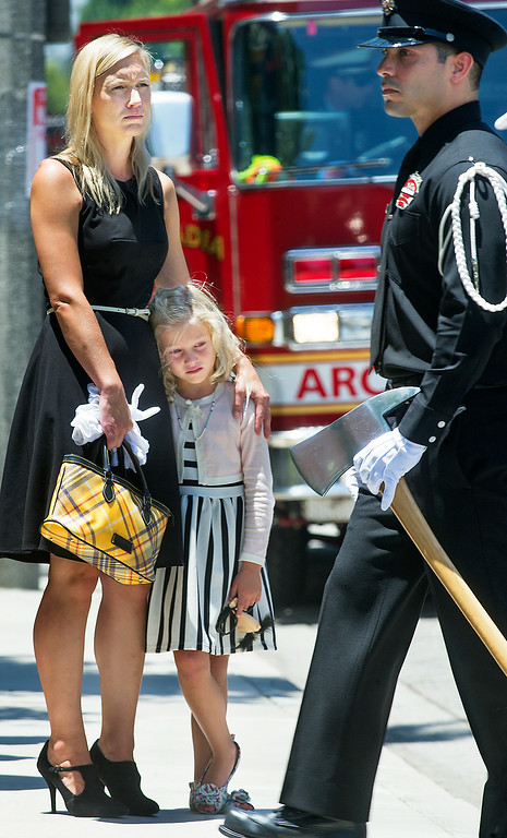 . Brigitte Herdman and daughter Sienna watching Michael Herdman coffin being loaded in hurst at memorial service on Wednesday, July 9, 2014, for the Arcadia firefighter-paramedic found dead in the Los Padres National Forest last Friday. Herdman, an avid adventurer, died after becoming separated from his camping partner. He fell from a cliff and was killed by his injuries. Searchers canvassed the forest for 11 days before finding his body.(Photo by Walt Mancini/Pasadena Star-News)