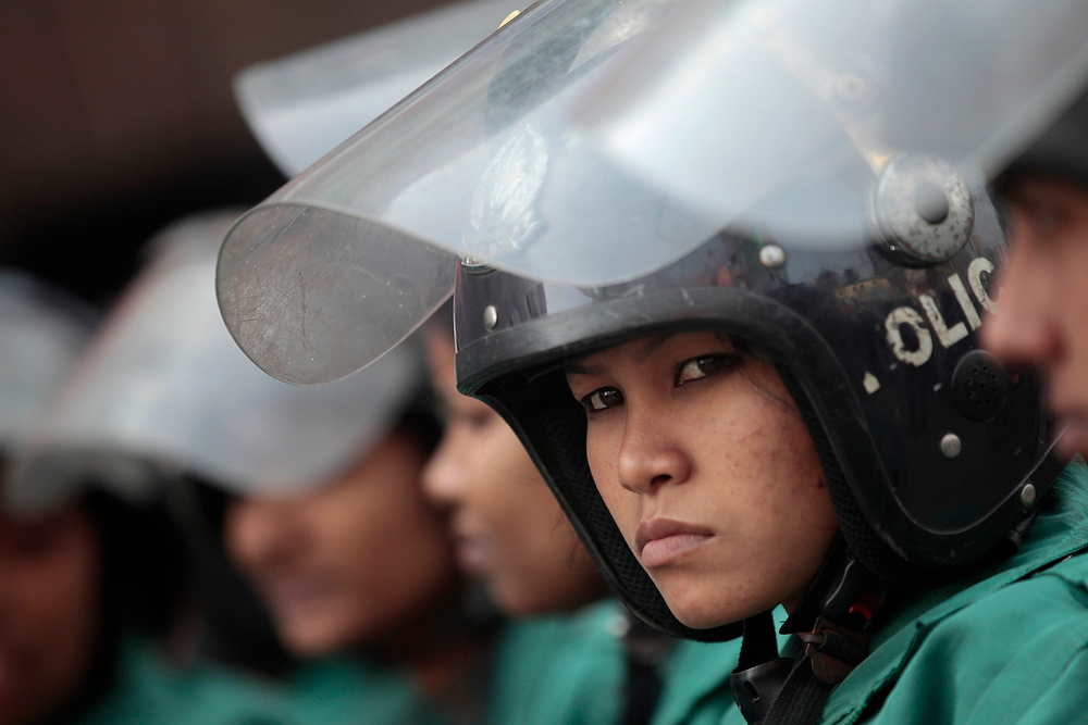 Description of . A police officer looks on as she stands with fellow officers in front of the head office of the Bangladesh Nationalist Party during a strike in Dhaka on December 13, 2012. Bangladesh's opposition alliance, led by former Prime Minister Begum Khaleda Zia, called for an eight-hours nationwide strike, two days after another violent strike, to press home its demand for immediate release of its acting secretary general Mirza Fakhrul Islam Alamgir and in protest against the killings and arrests of opposition activists during Sunday's road blockade program, local media reported.  REUTERS/Andrew Biraj