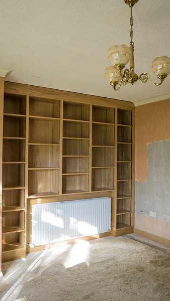 Oak veneered bookcase with full adjustable shelves, awaiting ceiling cove fitting to finish