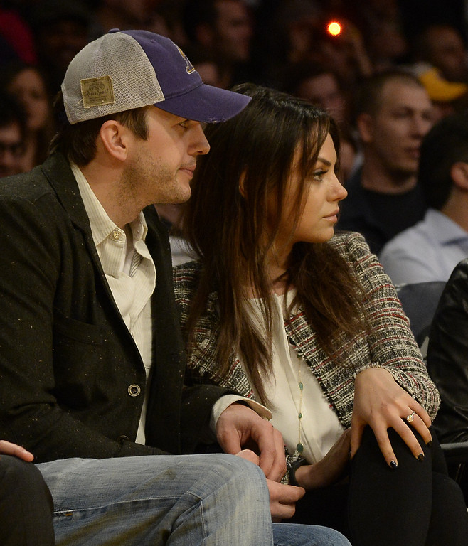 . US actor Ashton Kutcher (L) and his fiancee US actress Mila Kunis (C) attend the Los Angeles Lakers versus New Orleans Pelicans NBA game at the Staples Center in Los Angeles, California, USA, 04 March 2014.  EPA/MICHAEL NELSON