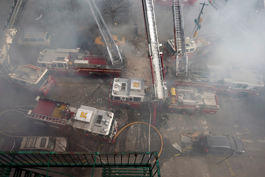 . Firefighters respond to a fire on 116th Street in Harlem after a building exploded in huge flames and billowing black smoke, leading to the collapse of at least one building and several injuries, Wednesday, March 12, 2014, in New York. (AP Photo/John Minchillo)