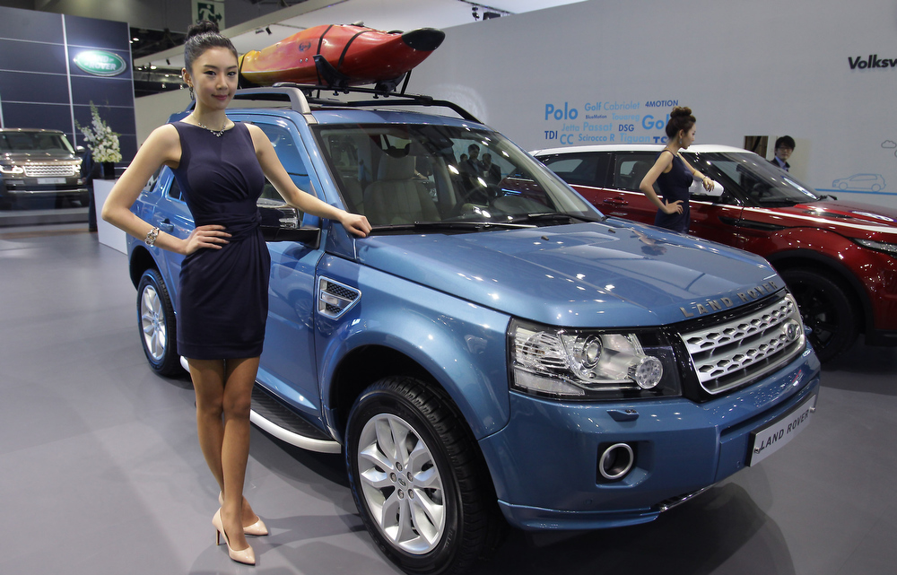 . A Model poses next to a Land Rover at the Seoul Motor Show 2013 on March 28, 2013 in Goyang, South Korea. The Seoul Motor Show 2013 will be held in March 29-April 7, featuring state-of-the-art technologies and concept cars from global automakers. The show is its ninth since the first one was held in 1995. About 384 companies from 14 countries, including auto parts manufacturers and tire makers, will set up booths to showcase trends in their respective industries, and to promote their latest products during the show.  (Photo by Chung Sung-Jun/Getty Images)