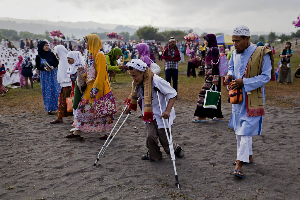 . YOGYAKARTA, INDONESIA - AUGUST 08:  Soleh, walks using crutch as he attends Eid Al-Fitr prayer on \'sea of sands\' at Parangkusumo beach on August 8, 2013 in Yogyakarta, Indonesia. Eid Al-Fitr, marks the end of Ramadan, the Islamic month of fasting and begins after the sighting of a new crescent moon.  (Photo by Ulet Ifansasti/Getty Images)