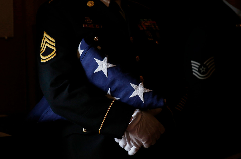 . A member of the military honor guard holds an American flag from Vice President Joe Biden\'s son, Beau Biden\'s casket during funeral services, Saturday, June 6, 2015, at St. Anthony of Padua Church in Wilmington, Del. (Kevin Lamarque/Pool Photo via AP)