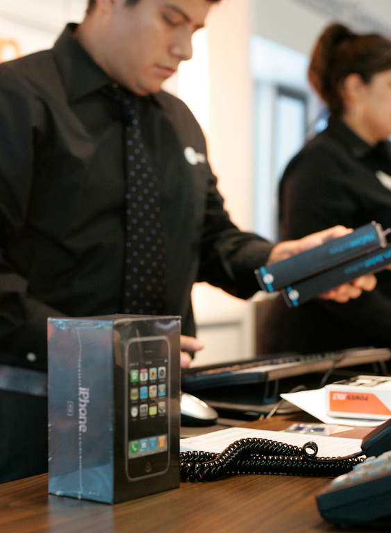 . Salesperson Miguel Salas rings up accessories to accompany the first Apple iPhone sold at the new AT&T Experience Store, in San Antonio, Texas, Friday, June 29, 2007. San Antonians began lining up at the store shortly after 10:00 am Friday. (AP Photo/J. Michael Short )