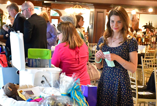 4/25/2019 Mike Orazzi | Staff Que Whiskey Kitchen's Brooke Kenyon looks for itmes in the silent auction during the Southington Chamber of Commerce's 81st Annual Dinner held at the Aqua Turf Club in Southington Thursday evening.