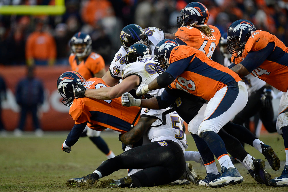 . Denver Broncos quarterback Peyton Manning (18) gets taken down in the third quarter. The Denver Broncos vs Baltimore Ravens AFC Divisional playoff game at Sports Authority Field Saturday January 12, 2013. (Photo by Joe Amon,/The Denver Post)